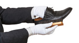 Shoeshiner in white gloves brushing black shoe poster