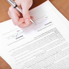 client signs an agreement by silver pen