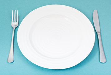 empty white plate with fork and knife on green
