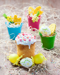 Easter cakes and colored eggs on a light wooden background