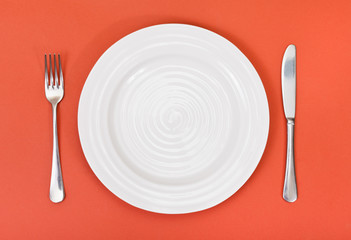 top view of white plate, fork, knife on red
