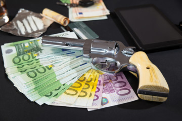 The gun, euro banknotes, drugs, tablet pc on black background