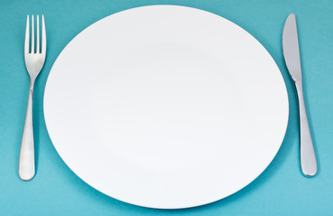 white porcelain plate with fork and knife on green
