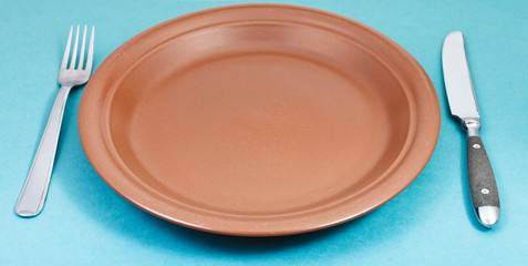 empty brown plate with fork and knife on green