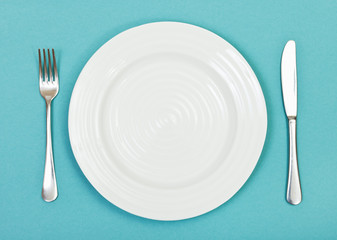 top view of white plate, fork, knife on green