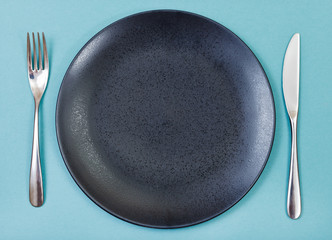 top view of black plate, fork, knife set on green