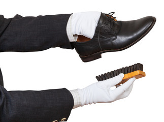 Shoeshiner in white gloves cleaning black shoes