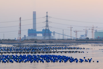 high voltage poles , crain , tower and many tanks floating above
