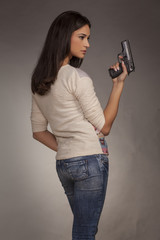 young woman posing with a gun on a gray background