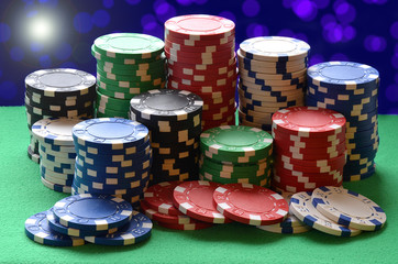 Red, blue, green, white and black poker chips pile
