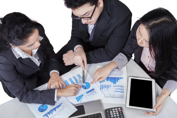 Business team pointing at pie chart