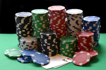 Red, blue, green, white and black poker chips pile and aces