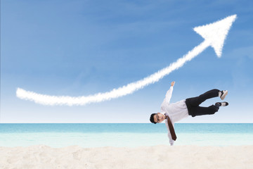 Acrobatic businessman perform success move at beach