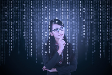 Businesswoman looking at binary code