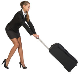 Businesswoman dragging heavy wheeled suitcase at utmost strain