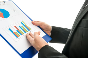 Side view of a businessman analysing a set of graphs over white