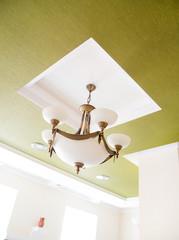 Vintage modern chandelier on green wall