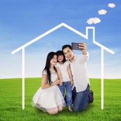 Family taking picture under a dream house