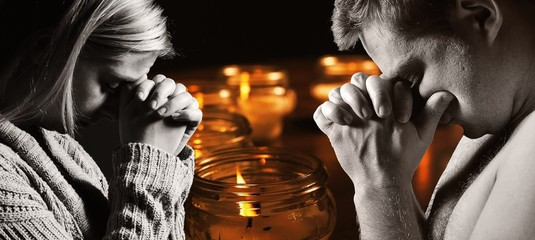 Praying man and woman with candles on background.