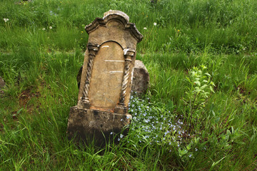 Fallen tombstone at an abandoned cemetery.