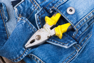 pliers in a pocket of jeans jacket