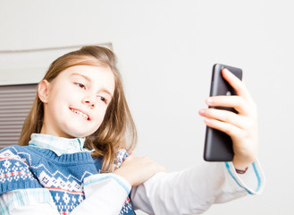 Little girl takes selfie with mobile phone