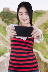 Girl taking self portrait at Great Wall of China