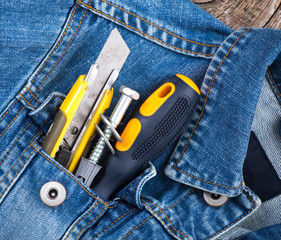 Tools, screwdriver, screw, stationary knife in blue jeans jacket