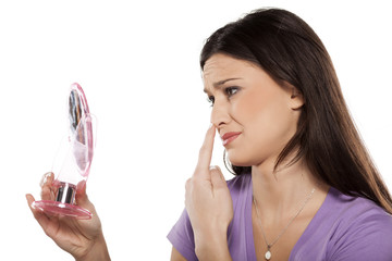unhappy girl touching her nose with the finger in the mirror