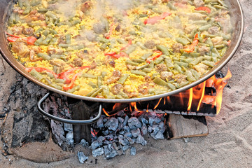 Traditional Spanish paella cooking over a wood fire