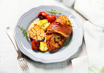 Chicken breast wrapped in parma ham with tomatoes
