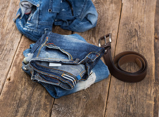 Dirty jeans and belt on wooden floor