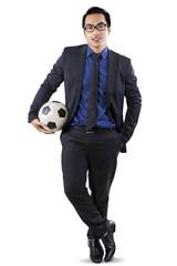 Male entrepreneur with soccer ball in studio