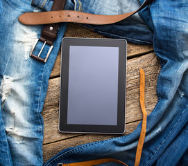 Jeans around mobile tablet pc on old wooden background