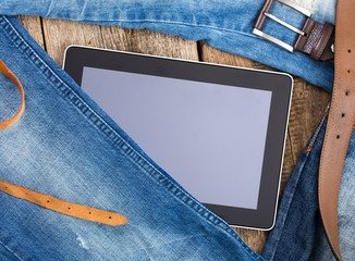 Jeans around mobile tablet pc on old wooben background