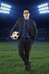 Male manager with football at field