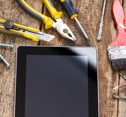 Different equipment tools of builder and tablet pc on wooden tex
