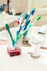 Five colorful toothbrushes in a water glass