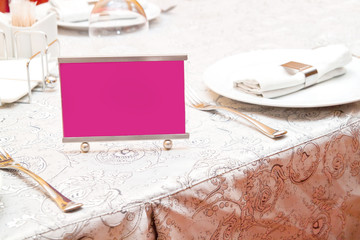 Pink Reserved sign on a table in restaurant