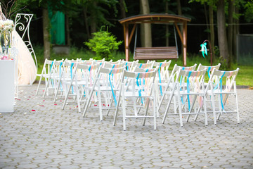 White wedding chairs decorated on ceremony