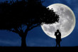 Silhouette of couple kissing on blue full moon