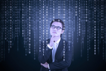 Thoughtful businessman looking at binary code