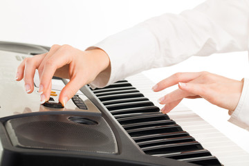 young hands of woman playing synthesizer isolated on white