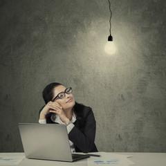 Young asian entrepreneur looking at lamp