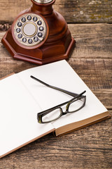 old telephone, glasses and book on wooden palette