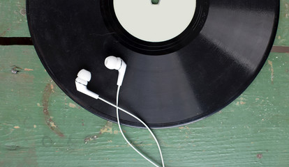 Black vinyl record disc with headphones on old green wooden desk