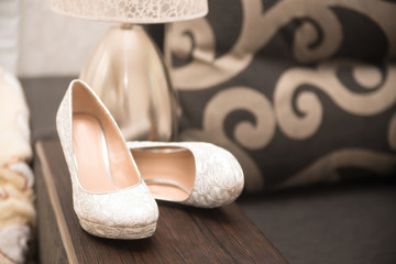 white wedding shoes with a bow and diamonds on a heel