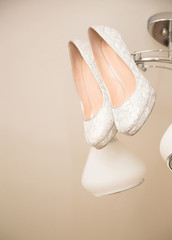 whithe high heel woman shoes hanging on chandelier