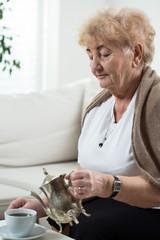 Senior woman pouring tea