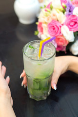 Woman hands with Mojito cocktail in a restaurant on a rustic woo
